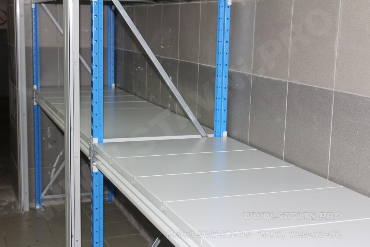 Синие перфорированные рамы качественного стеллажа внутри роллетного шкафа