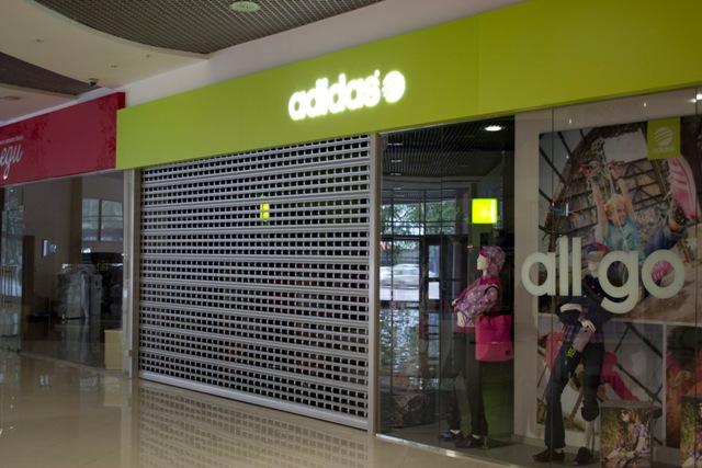 алюминиевая рольрешетка серого цвета на входе в бутик адидас
