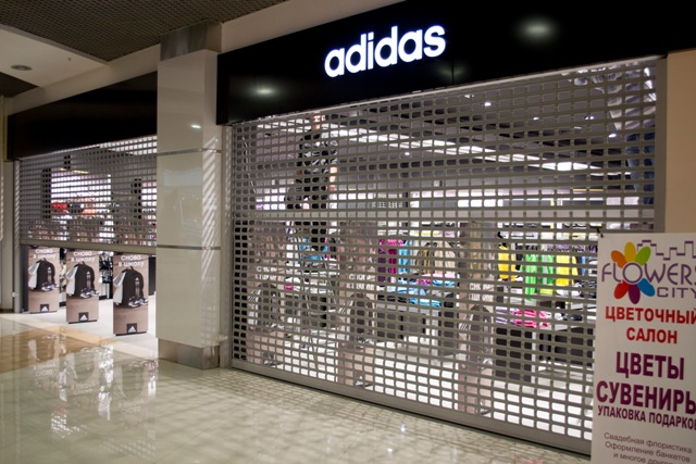 алюминиевая рольрешетка серого цвета на входе в магазин адидас