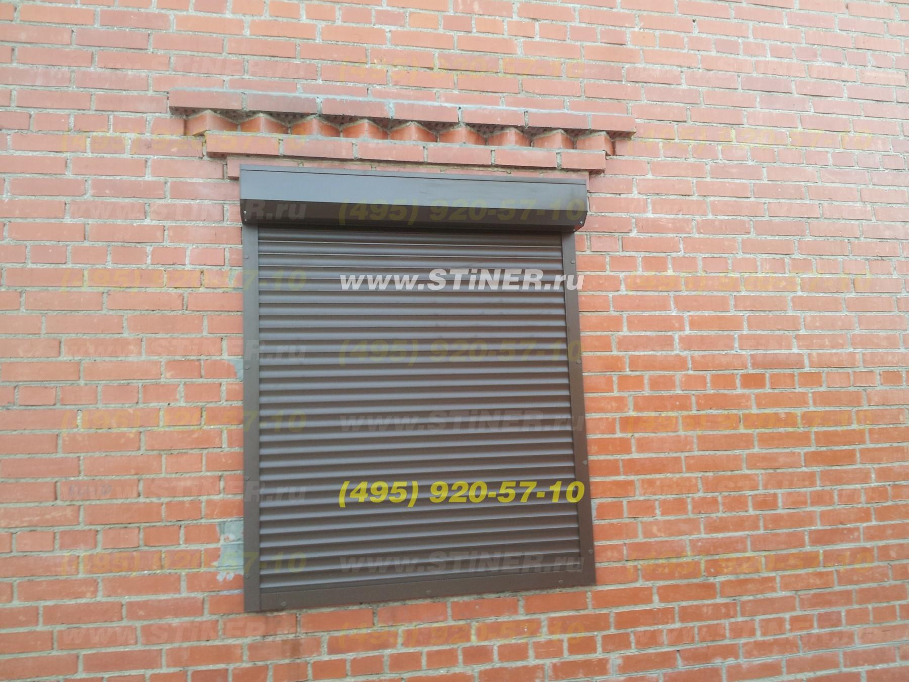 установленные защитные жалюзи на доме из красного кирпича